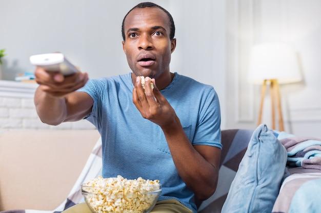 Bonito hombre guapo asombrado comiendo palomitas de maíz y estar involucrado en la película mientras ve la televisión