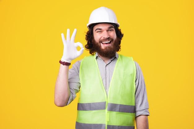 Un bonito joven arquitecto barbudo está mirando alegre a la cámara que muestra el cartel de ok cerca de una pared amarilla