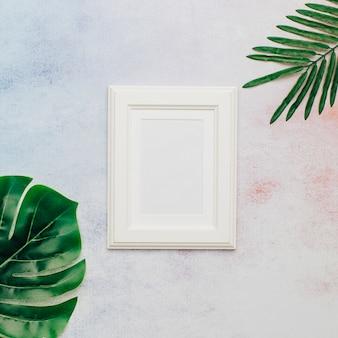 Bonito marco blanco con hojas tropicales