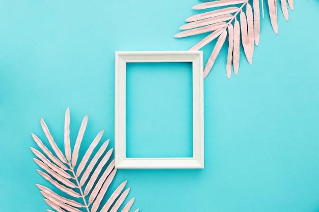 Bonito marco blanco sobre fondo azul con hojas de palma rosa