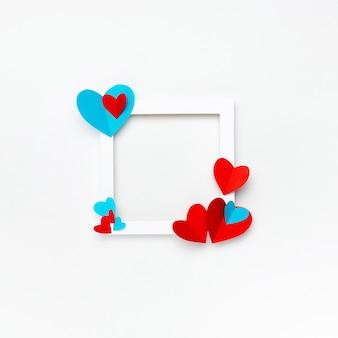 Bonito marco cuadrado blanco con copyspace para texto sobre fondo blanco decorado con corazones de papel hecho a mano