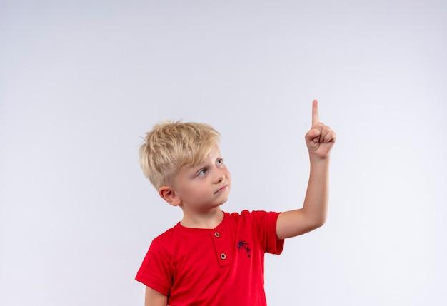Un bonito niño con cabello rubio y ojos azules vistiendo una camiseta roja apuntando hacia arriba con el dedo índice sobre una pared blanca