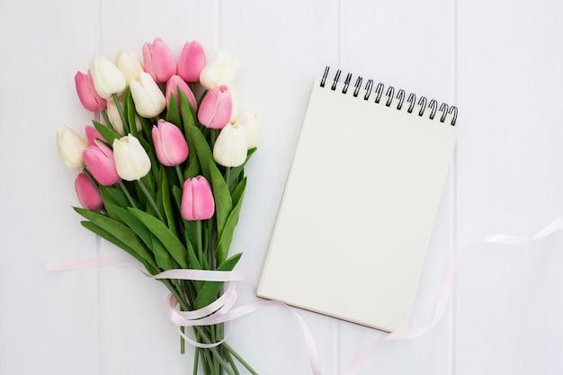 Bonito ramo de flores de tulipanes con cuaderno vacío.