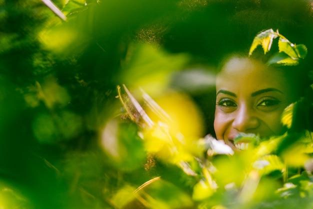Bonito retrato de hermosa mujer afro a través de las hojas. enfoque selectivo.