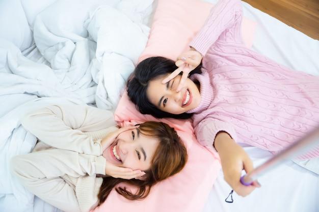 Bonitos amigos adolescentes selfie en la cama en casa