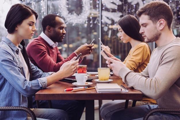 Bonitos cuatro amigos melancólicos mirando los teléfonos mientras se reúnen en el café y guardan silencio