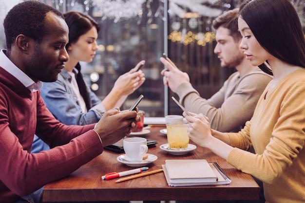 Bonitos cuatro amigos ocupados usando teléfonos mientras están sentados en la cafetería y mirando hacia abajo