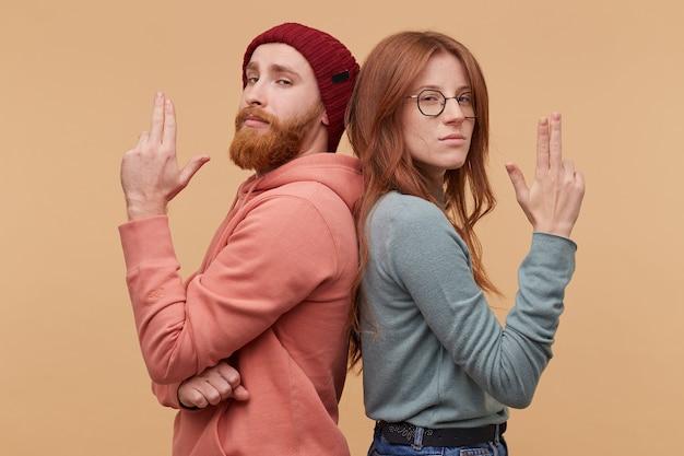 Bonnie y clyde sr. y sra. smith. chico barbudo y la chica están espalda con espalda