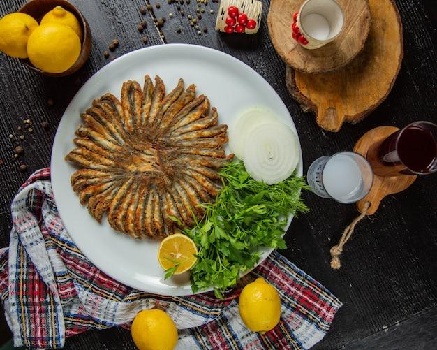 Boquerones fritos con limón y hierbas.