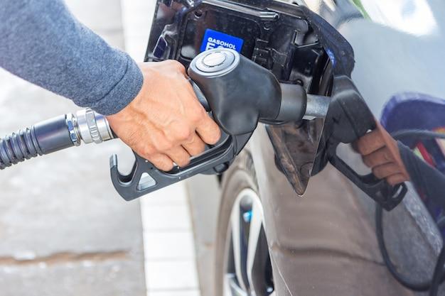 Boquilla de combustible agregar combustible en el coche en la estación de servicio