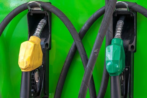 Boquillas de la bomba de gas amarillo y verde en una estación de servicio, boquilla vfuel en la estación de petróleo tailandia