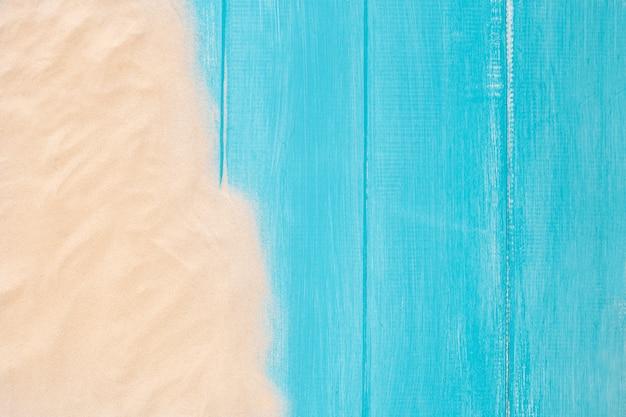 Borde de la arena en el fondo de madera azul con espacio de copia