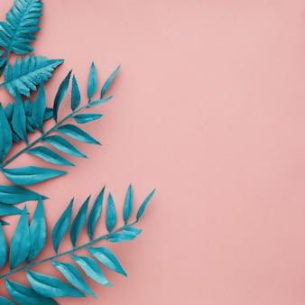 Borde azul hojas sobre fondo rosa con copyspace