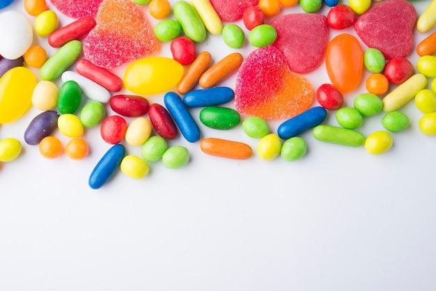 Borde de coloridos caramelos de gelatina en blanco