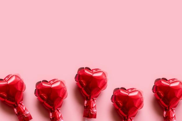 Borde de corazones de globos de papel rojo sobre fondo rosa