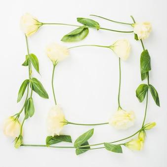 Borde de marco en blanco hecho con flores sobre fondo blanco