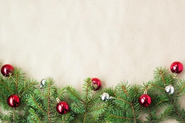 Borde festivo de navidad con bolas rojas y plateadas en ramas de abeto y copos de nieve sobre fondo beige rústico