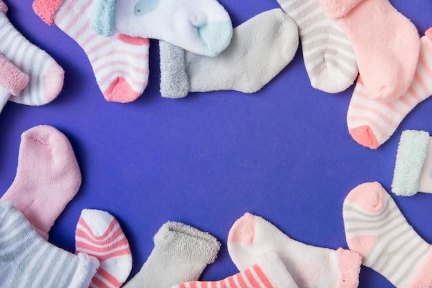 Borde hecho con muchos calcetines de bebé sobre fondo azul