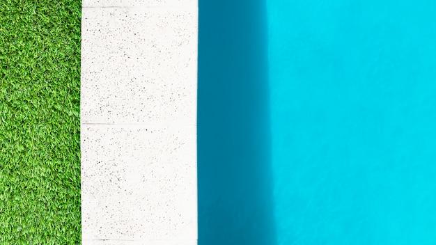 Borde de hierba, borde de piedra y agua de piscina.