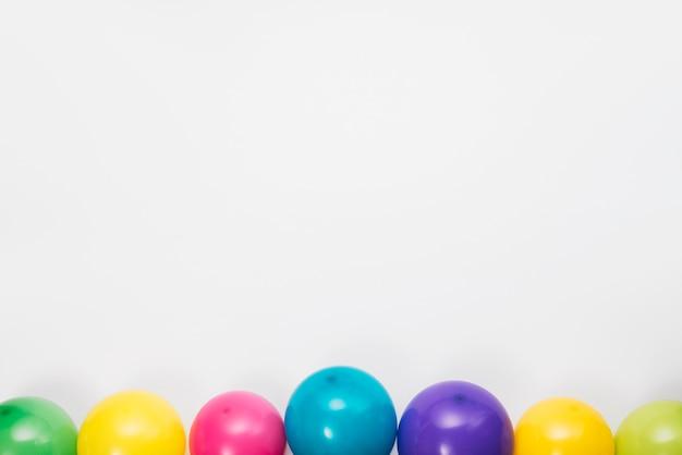 Borde inferior hecho con globos de colores sobre fondo blanco