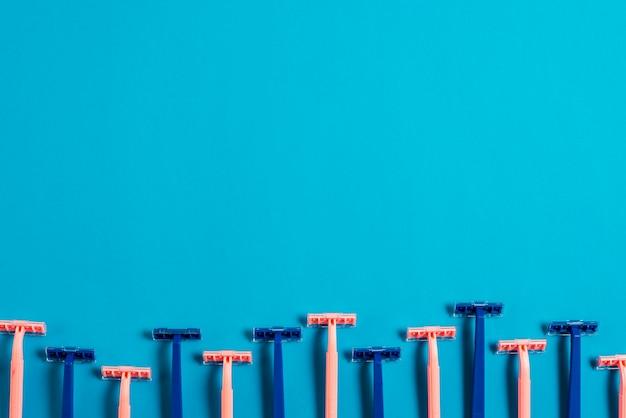 Borde inferior hecho con maquinillas de afeitar de color rosa y azul sobre fondo azul