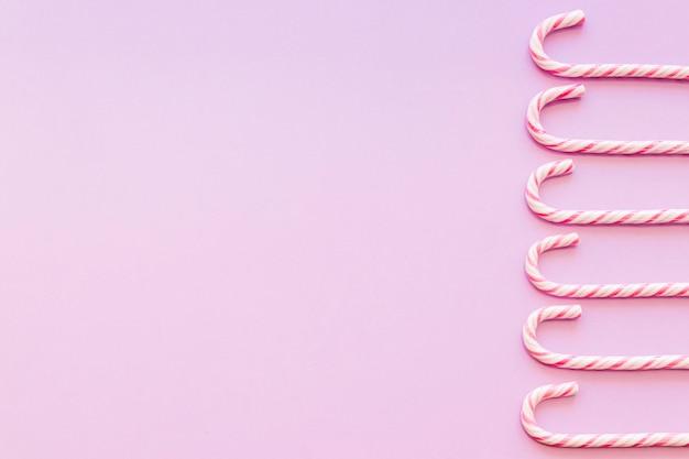 Borde lateral hecho con dulces de caña de navidad sobre fondo rosa