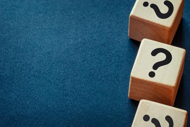 Borde lateral de signos de interrogación en cubos de madera.