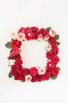 Borde de marco cuadrado de flores rosas rosadas, rojas sobre superficie blanca