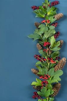 Borde del marco decorativo, rama con frutos rojos, hojas verdes y conos de abeto