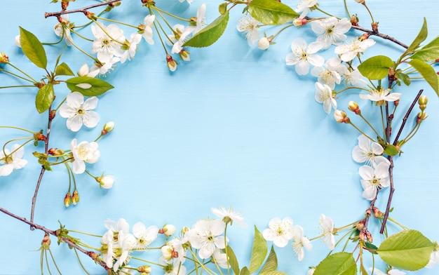 Borde de marco de flor de primavera sobre fondo azul. flores de primavera con lugar para el texto. concepto del día de la madre