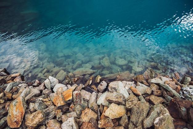 Borde pedregoso del lago de montaña azul