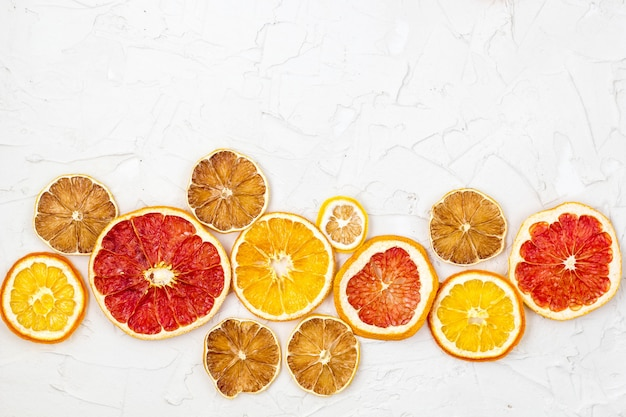 Borde de rodajas secas de varios cítricos sobre fondo blanco. naranja limón pomelo copyspace