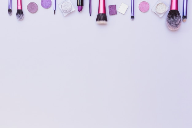 Borde superior arreglado con productos cosméticos sobre fondo blanco