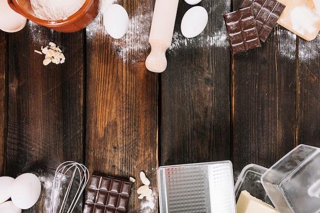 Borde superior e inferior hecho con ingredientes para hornear con utensilios de cocina en tablas de madera