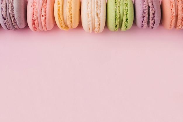 Borde superior hecho con macarrones de colores sobre fondo rosa
