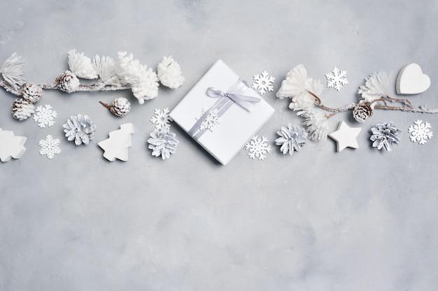 Borde una tarjeta de felicitación de navidad con caja de regalo de navidad, conos, corazón, copos de nieve