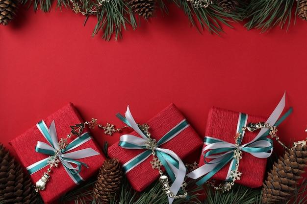 Borde con tres giftbox de navidad en papel rojo y cintas sobre superficie roja. vista superior. espacio para deseos