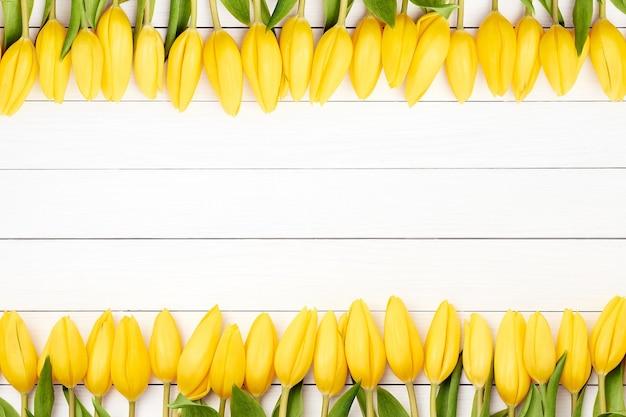 Borde de tulipanes amarillos en madera blanca.