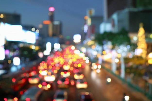 Borrosa de atasco de tráfico en la ciudad con el cielo crepuscular y la iluminación del edificio.