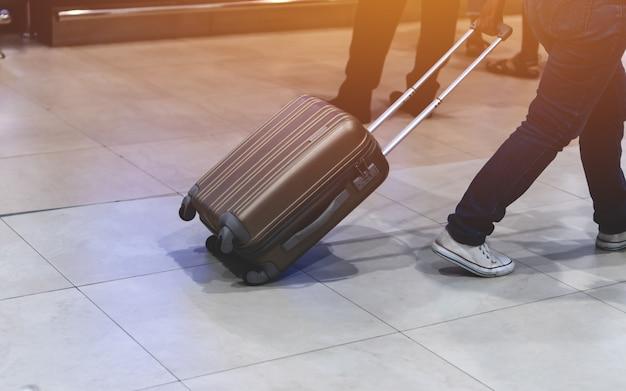 Borrosa de equipaje de viajero viajero caminando en la terminal del aeropuerto para registrarse con destello de luz. concepto de viajes y vacaciones