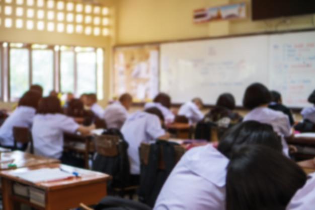 Borrosa de los estudiantes de secundaria del grupo asiático con uniformes en el aula