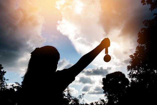 Borrosa de manos de silueta planteadas y celebración de medallas de oro con cinta