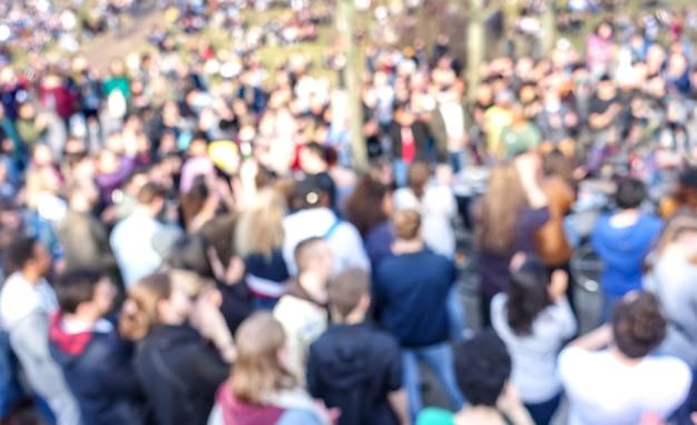 Borrosa multitud desenfocada de personas en el espacio público