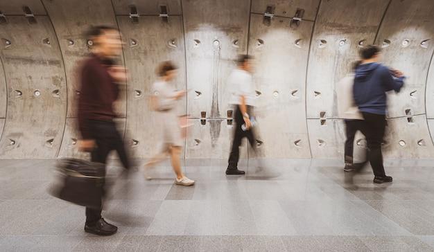 Borrosa multitud de empresarios irreconocibles caminando en el moderno túnel del metro en la hora pico de la jornada laboral