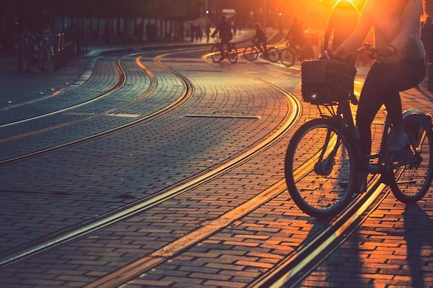 Borrosa de personas montando bicicleta durante la puesta de sol en la ciudad de burdeos en estilo vintage y textura de grano con espacio de copia