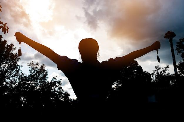 Borrosa de silueta busunesswoman manos levantadas y la celebración de medallas de oro con la cinta contra el fondo puesta de sol para mostrar el éxito del equipo en los negocios, los ganadores concepto de premio de éxito.