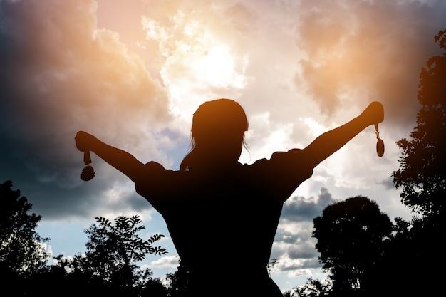 Borrosa de silueta empresaria manos levantadas y sosteniendo gol