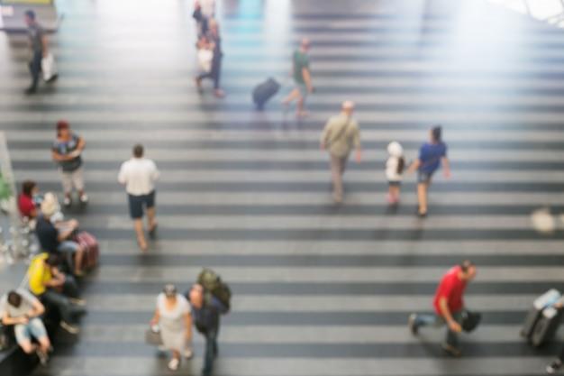 Borrosos pasajeros caminando en el área de la estación de tren o en la terminal del aeropuerto.