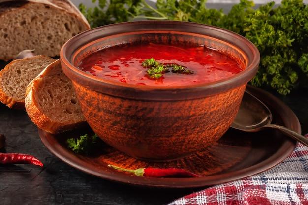 Borsch - sopa de remolacha en un cuenco de barro sobre un fondo de piedra, plato tradicional de la cocina ucraniana.