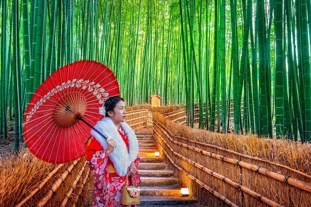 Bosque de bambú. mujer asiática vistiendo un kimono tradicional japonés en el bosque de bambú en kyoto, japón.